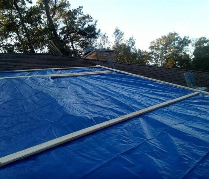 the blue tarp is secured to the damaged roof