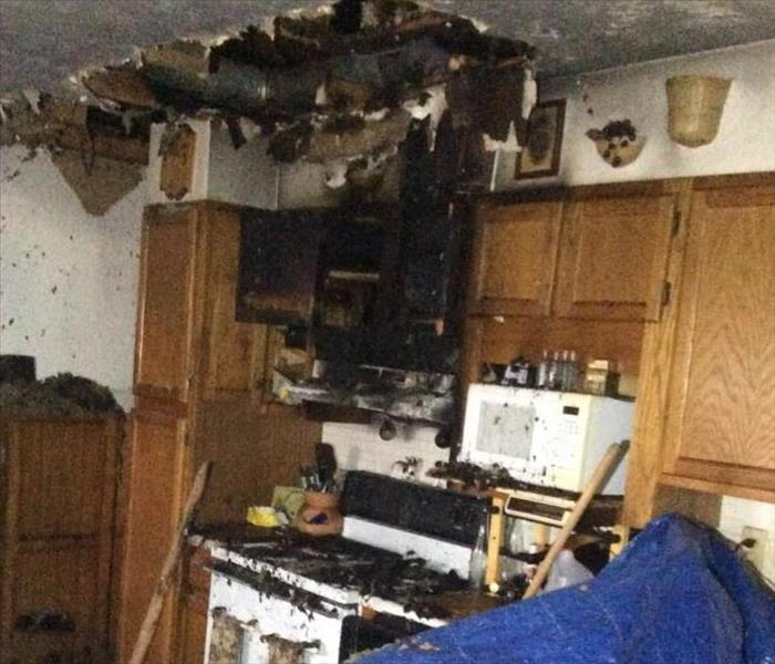 kitchen with stove, cabinets and ceiling burned after a fire