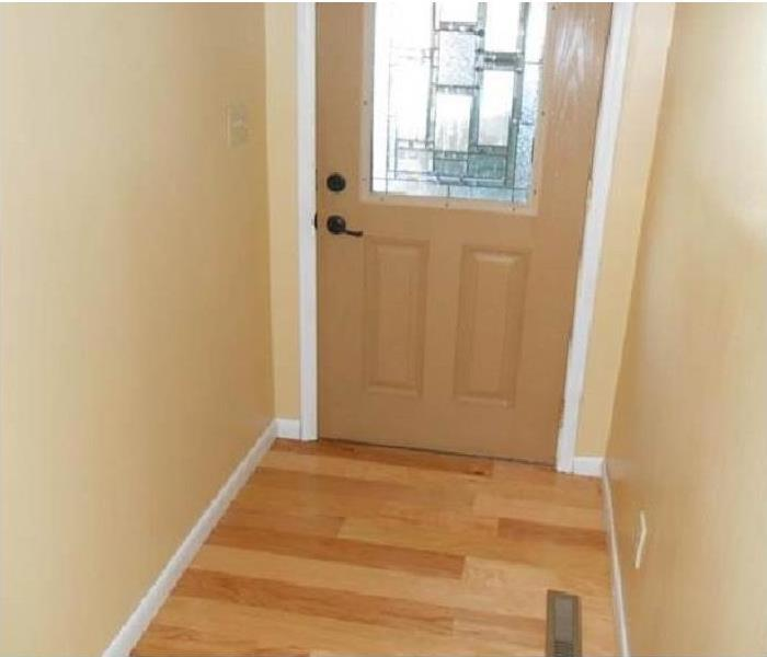 the trim around the door is new along with the hardwood flooring and freshly painted walls