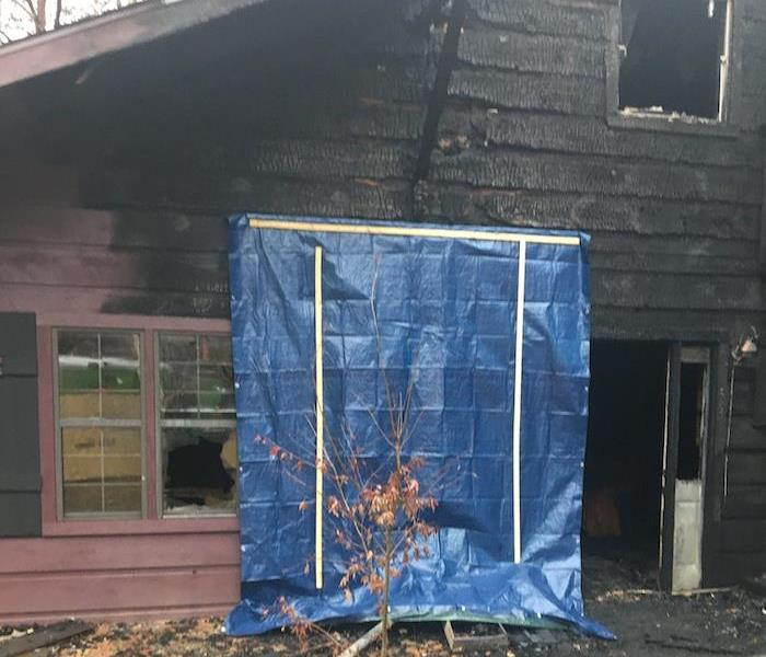 Residence with fire damage and a tarp over a window