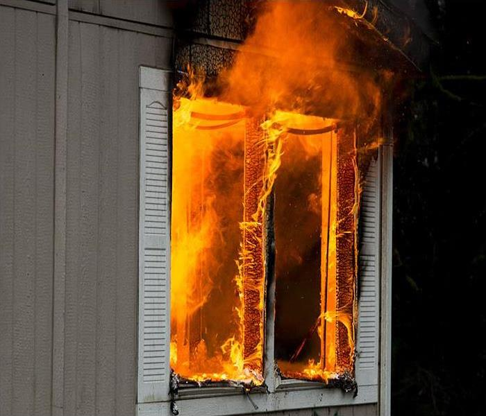 Flames shooting out of a small window in a burning home