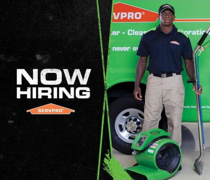 Male employee standing in front of a SERVPRO van with Now Hiring text on the side