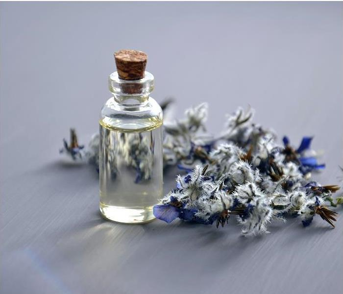 Essential oil with flower sprig in background